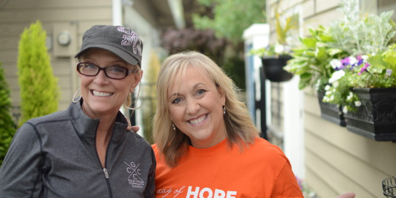 Women smile for camera while volunteering for Day of Hope.